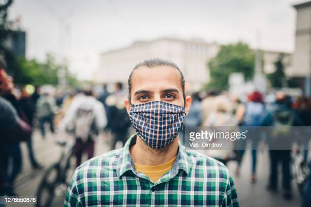 young man with a mask surrounded by a crowd in the city. air pollution / coronavirus protection / protest concept. - striker stock pictures, royalty-free photos & images
