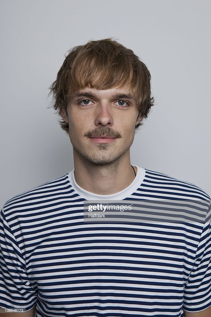 A young man with a mustache wearing a striped t-shirt : Stock Photo