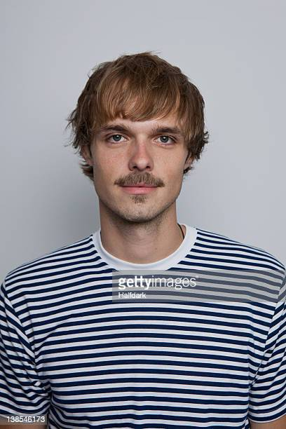 A young man with a mustache wearing a striped t-shirt