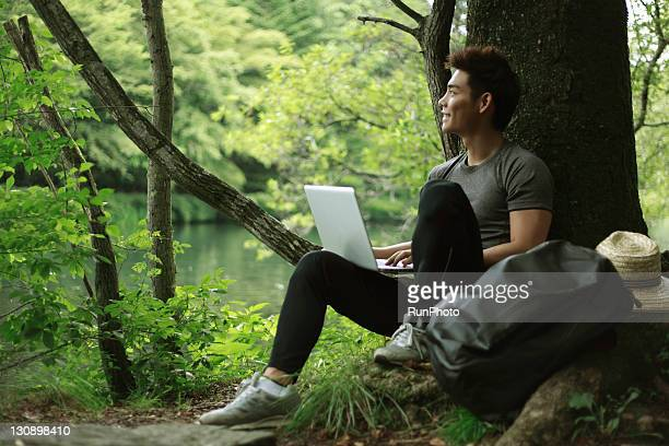 young man with a notebook pc in the forest - アウトドア ストックフォトと画像