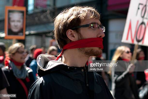 Young man with a red gag marches in a protest against rising university tuition fees in the Province of Québec.