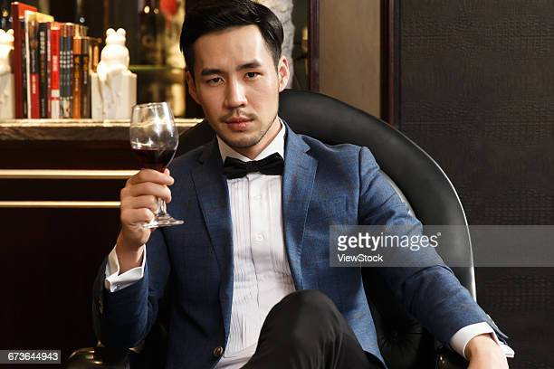 A young man with a red wine glass