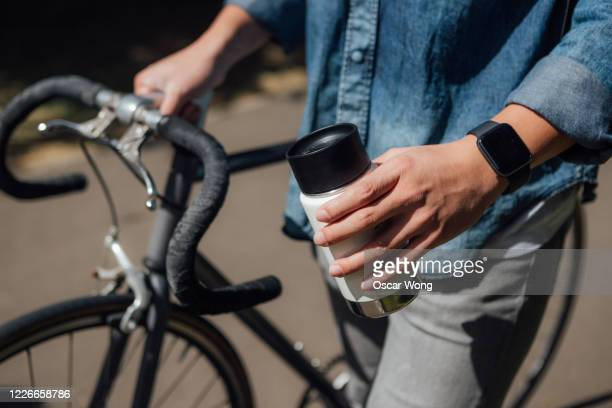 young man with a reusable coffee cup commuting by bike - close up stock pictures, royalty-free photos & images