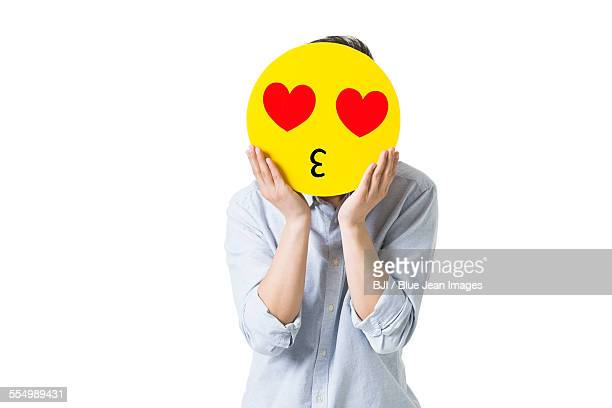 Young man with a romantic emoticon face in front of his face