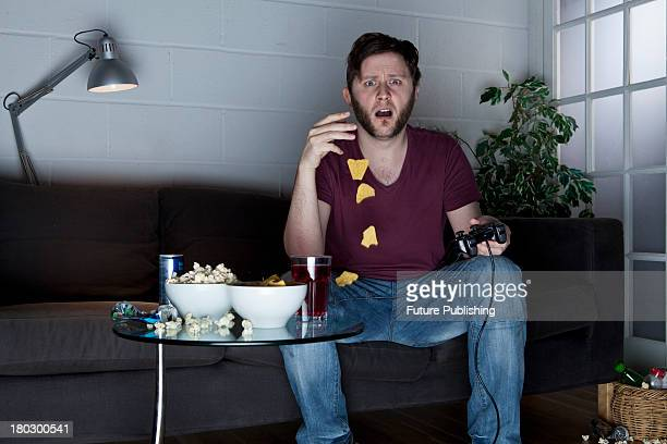 A young man with a shocked expression dropping tortilla chips while playing Sony PlayStation 2 video games on a sofa taken on July 9 2013