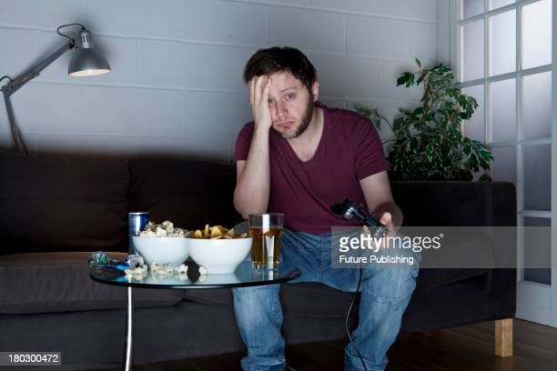 A young man with a sleepy expression playing Sony PlayStation 2 video games on a sofa alongside a table of snacks taken on July 9 2013
