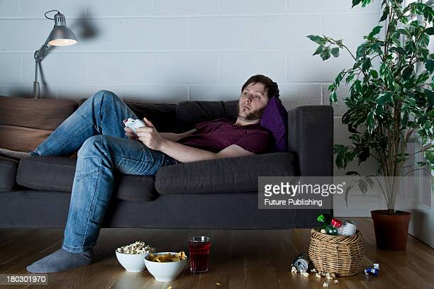 Young man with a sleepy expression playing XBox 360 video games while lying on a sofa with bowls of snacks, taken on July 9, 2013.