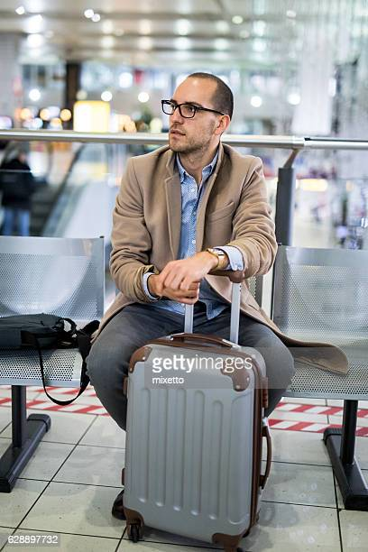Young man with a suitcase in lounge