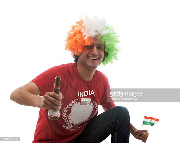 Young man with a wig holding a beer bottle