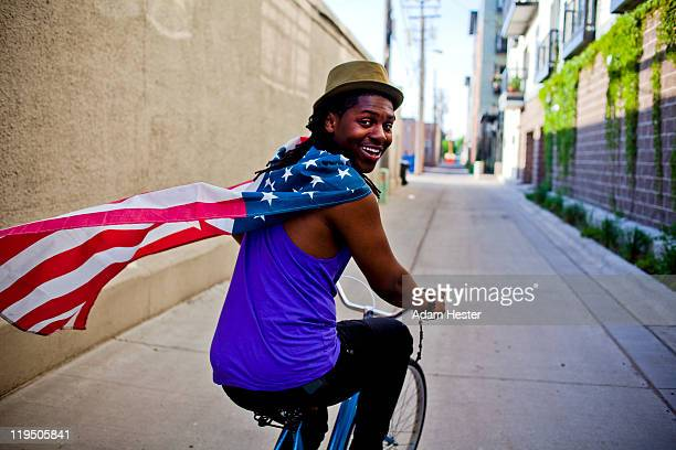 a young man with an american flag around his neck. - american culture stock pictures, royalty-free photos & images