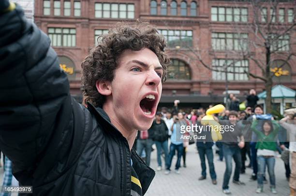 CONTENT] A young man with an enviably full head of hair photographed close with a wideangle lens as he raises his arm to yell Onlookers encourage him