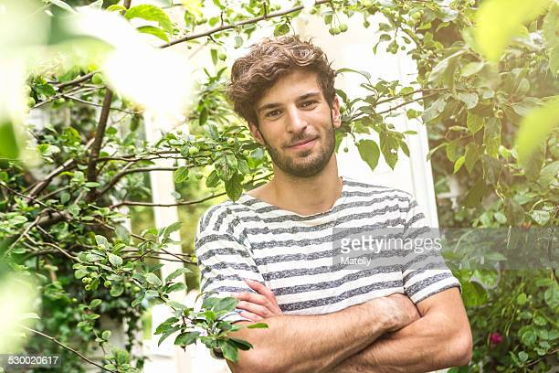 young man with arms crossed in garden - alleen één jonge man stockfoto's en -beelden