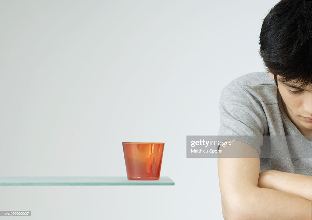 Young man with arms folded and head down : Stockfoto