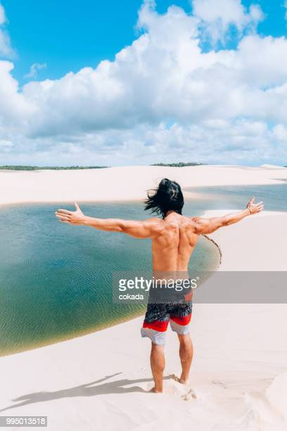 young man with arms open on the sands of lençois maranhenses - lencois maranhenses national park stock pictures, royalty-free photos & images
