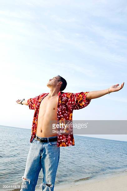 young man with arms outstretched at beach - fully unbuttoned stock pictures, royalty-free photos & images