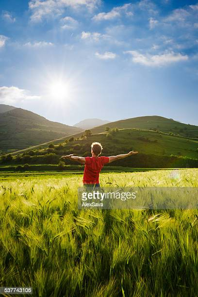 young man with arms outstretched enjoying the sunset