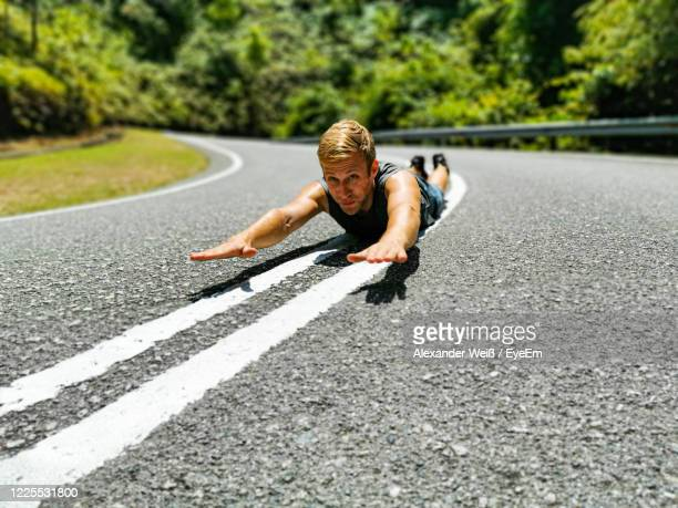 young man with arms raised lying on road during sunny day - weiß stock pictures, royalty-free photos & images