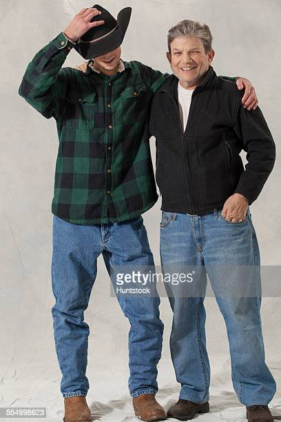 Young man with autism adjusting his hat with his mentor arm in arm