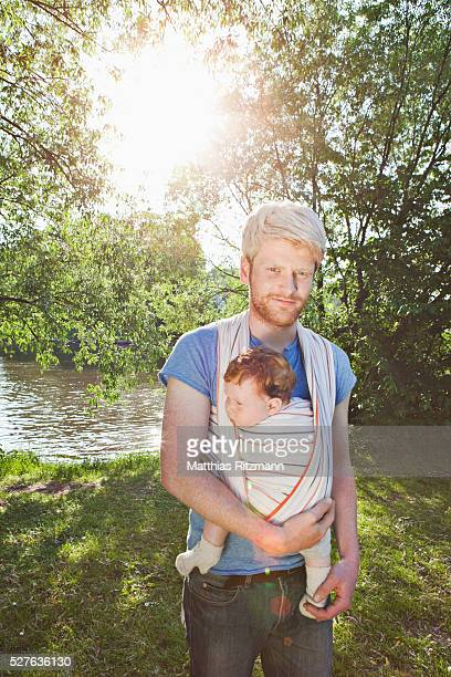Young man with baby (6-12 months) in baby carrier standing in park