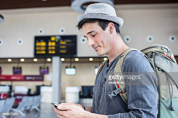 young man with backpack and cell phone in airport - 20 29 years stock pictures, royalty-free photos & images