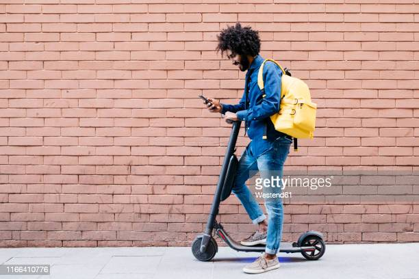 young man with backpack and e-scooter standing in front of brick wall looking at cell phone - 移動中 ストックフォトと画像