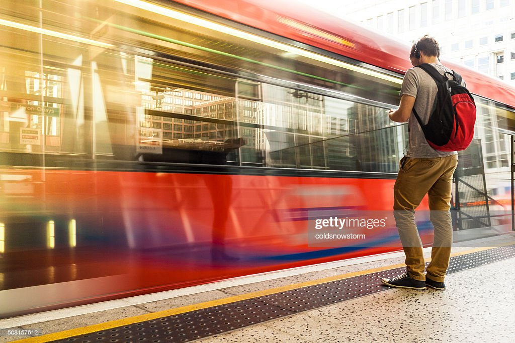 Young man with backpack and headphones waiting for train : Stock Photo