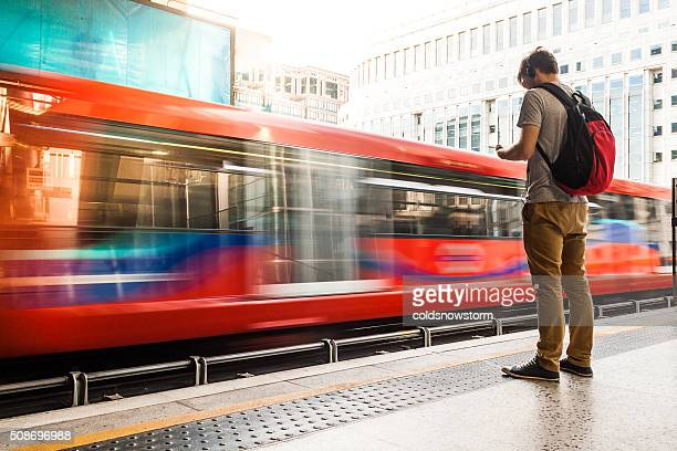 young man with backpack and headphones waiting for train - underground stock photos and pictures