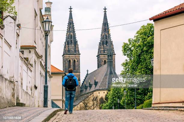Young man with backpack exploring streets of Prague old town, Czech Republic