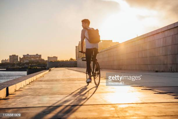 young man with backpack riding bike on waterfront promenade at the riverside at sunset - radfahren stock-fotos und bilder