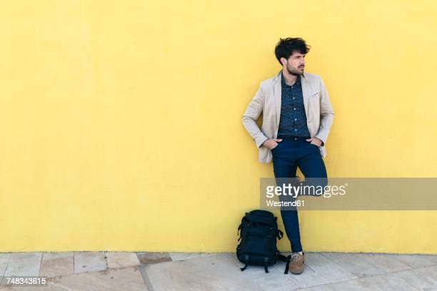 Young man with backpack standing in front of yellow wall