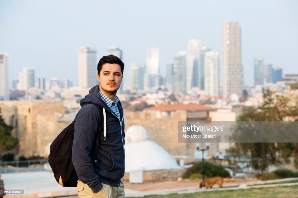 Young man with backpack standing with skyscrapers skyline in the background, Tel Aviv, Israel : Stock Photo