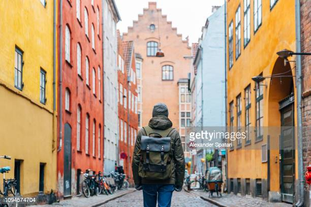 young man with backpack walking in the streets of copenhagen old town - copenhagen stock pictures, royalty-free photos & images