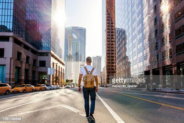young man with backpack walking on the street in los angeles downtown, california, usa - city of los angeles fotografías e imágenes de stock