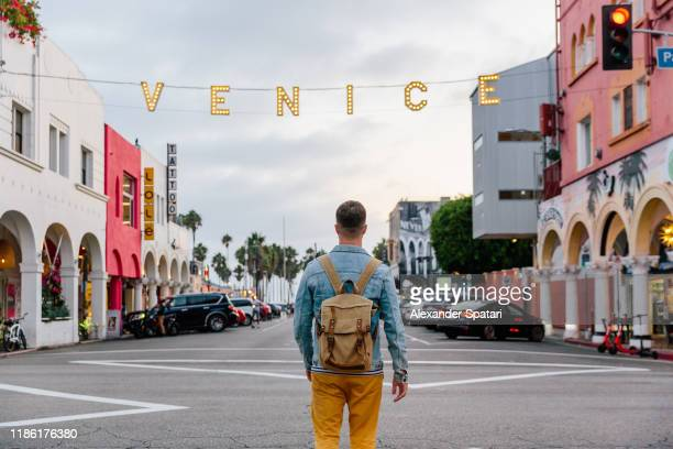 young man with backpack walking on the street to venice beach in los angeles, california, usa - de stad los angeles stockfoto's en -beelden
