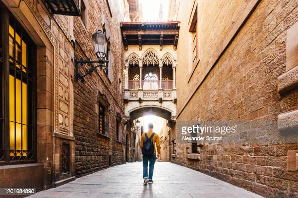 young man with backpack walking on the streets of gothic quarter in barcelona, spain - barcelona spain stock pictures, royalty-free photos & images