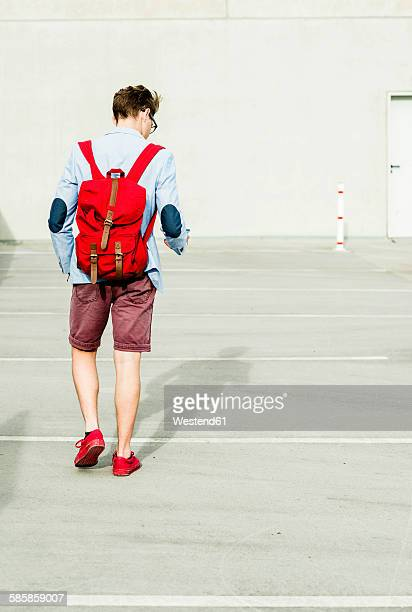 Young man with backpack walking outdoors looking on cell phone
