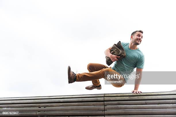 young man with bag jumping over bench - ease stock pictures, royalty-free photos & images