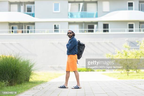 young man with bag, sunglasses, cap and shorts in the city, freiburg, baden-wuerttemberg, germany - sigrid gombert imagens e fotografias de stock