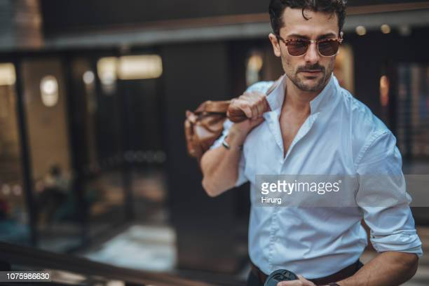 young man with bag walking on the street - leather shirt stock pictures, royalty-free photos & images
