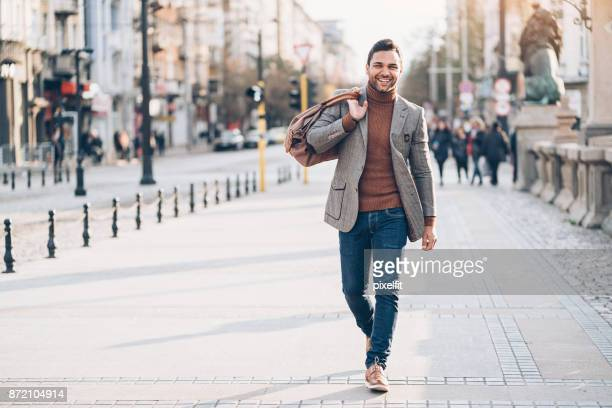 young man with bag walking on the street - a fall from grace stock pictures, royalty-free photos & images