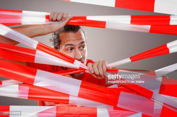 young man with barrier tape in red and white, corona crisis, germany - 非常線 ストックフォトと画像