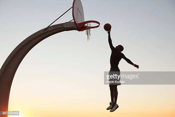 Young man with basketball, jumping towards net, outdoors