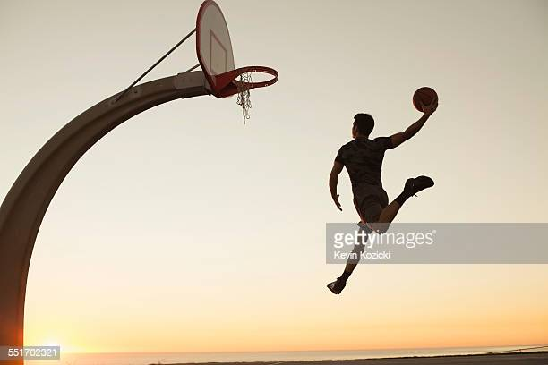 Young man with basketball, jumping towards net, rear view, outdoors