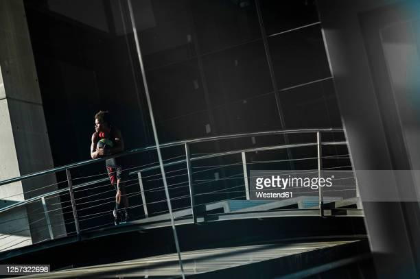 young man with basketball standing at a modern building in the city - 18 19 years stock pictures, royalty-free photos & images