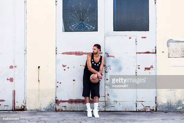 Young man with basketball wearing basecap