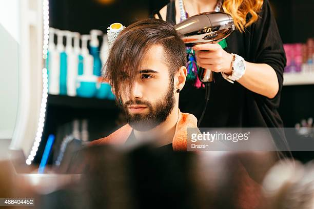 Young man with beard at hairdressers faning his brown hair