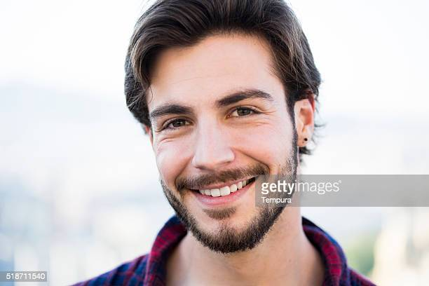 Young man with beard looking at camera.