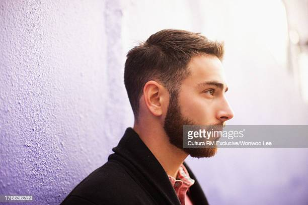 Young man with beard looking away against purple wall