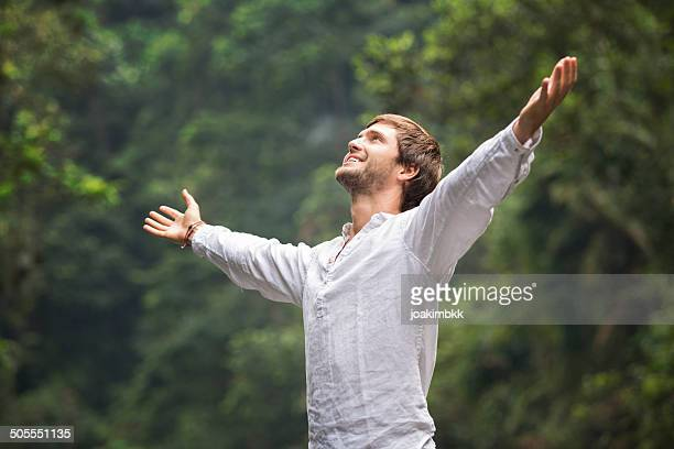 Young man with beard stretches arms to embrace freedom