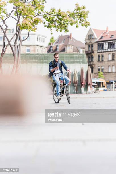 Young man with bicycle in the city using cell phone